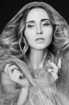 Vrouw gehuld in paarse stof, mooi slank figuur, zuiverheid en integriteit. luxe naakte naakte vrouw. naakte vrouw kunst in lila lichte transparante jurk die zich voordeed op een donkere muur