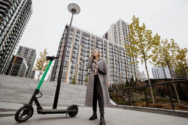 Vrouw gehuurde scooter. herfst in grote stad. aantrekkelijke vrouw in vrijetijdskleding bespreekt voorwaarden voor het huren van scooter door zijn smartphone. flatblokken op achtergrond. elektrische scooters voor openbaar aandeel.