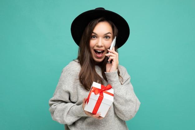 Vrouw geïsoleerd op blauwe achtergrond muur dragen zwarte hoed en grijze trui houden geschenkdoos praten op mobiele telefoon en camera kijken.