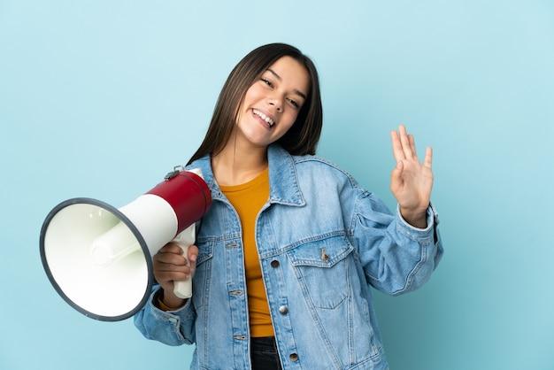 Vrouw geïsoleerd op geel met een megafoon en groet met hand met gelukkige uitdrukking
