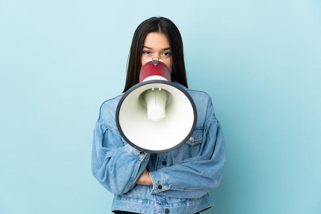 Vrouw geïsoleerd op geel schreeuwen door een megafoon om iets aan te kondigen