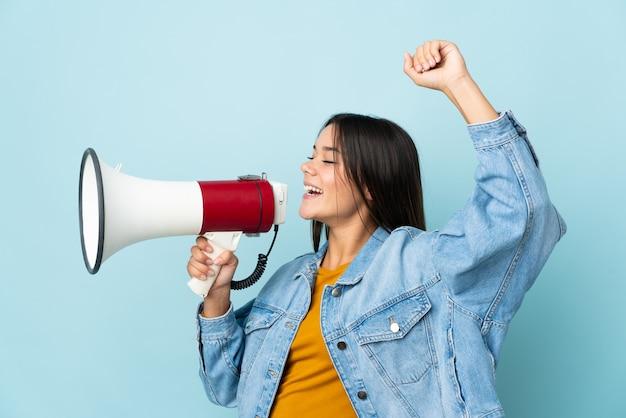 Vrouw geïsoleerd op geel schreeuwen door een megafoon om iets in laterale positie aan te kondigen