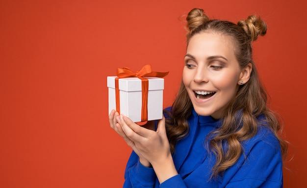 Vrouw geïsoleerd op kleurrijke achtergrond muur dragen stijlvolle casual kleding bedrijf geschenkdoos en op zoek naar de zijkant.