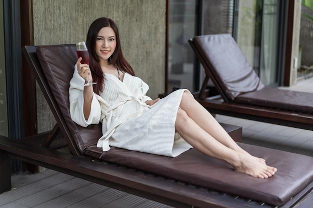 Vrouw gekleed badjas zittend op strandstoel in het zwembad