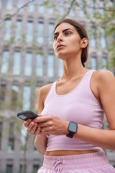 Vrouw gekleed in activewear gebruikt mobiele telefoon voor het vinden van routewandelingen in de stad, gericht op afstand, geniet van sportactiviteiten en gaat cardiotraining doen