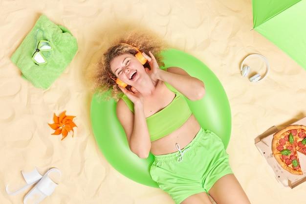 Vrouw gekleed in bijgesneden top en korte broek geniet van het luisteren van muziek via koptelefoon poses op zandstrand alleen eet pizza ligt op groene opgeblazen zwemmen.