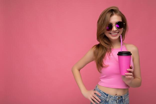Vrouw, gekleed in casual stijlvolle kleding geïsoleerd over kleurrijke muur met papieren kopje koffie drinken. lege ruimte