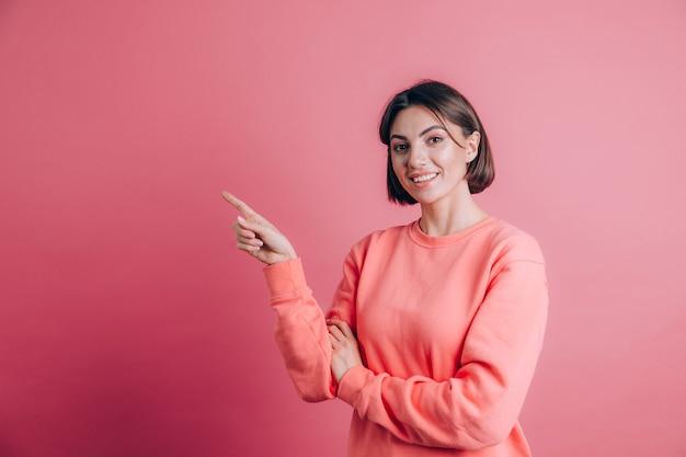 Vrouw, gekleed in casual trui op achtergrond blij gezicht lachend kijken naar de camera. wijs met wijsvinger naar links.