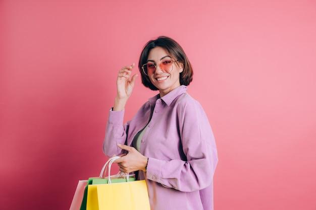 Vrouw, gekleed in casual trui op achtergrond gelukkig genieten van winkelen met kleurrijke tassen dragen zomer zonnebril