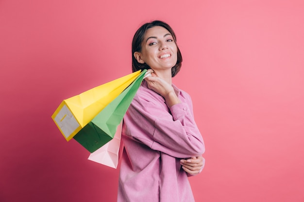 Vrouw, gekleed in casual trui op achtergrond gelukkig genieten van winkelen met kleurrijke tassen