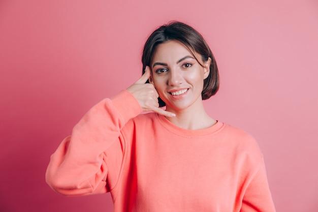 Vrouw, gekleed in casual trui op achtergrond glimlachend telefoongebaar met hand en vingers doen zoals praten aan de telefoon