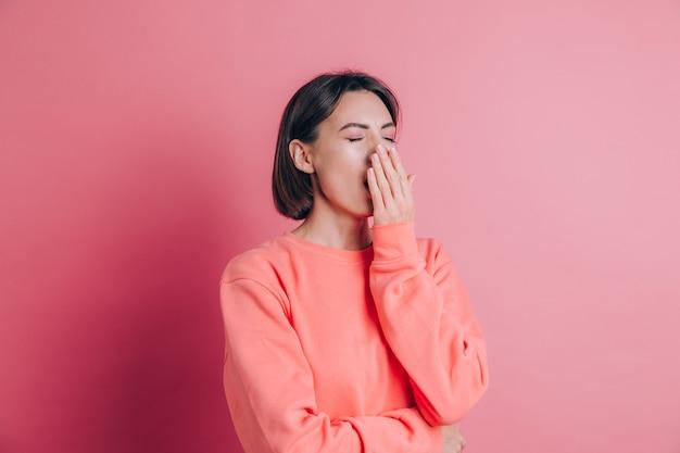 Vrouw, gekleed in casual trui op achtergrond verveeld geeuwen moe die mond bedekken met de hand. rusteloos en slaperig