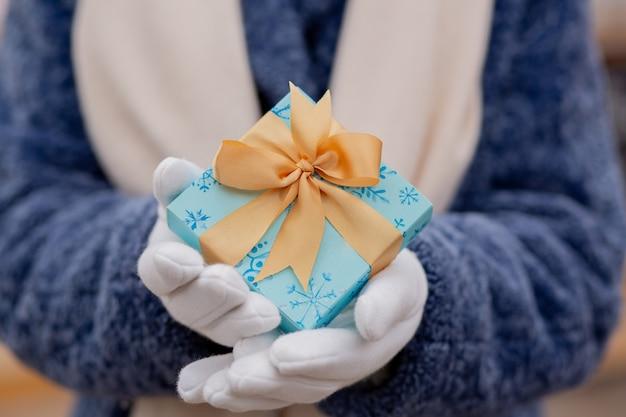 Vrouw gekleed in een blauwe winterjas met een kleine geschenkdoos met een zijden lint op straat