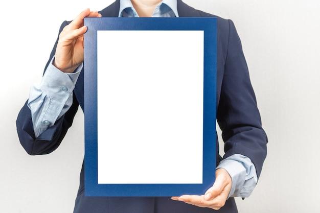 Vrouw gekleed in een pak houdt een mockup van een frame-afbeelding vast