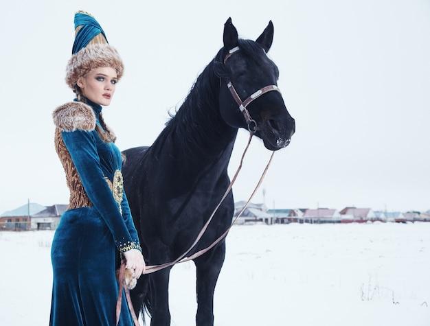 Vrouw gekleed in een prachtige jurk in winterlandschap met paard
