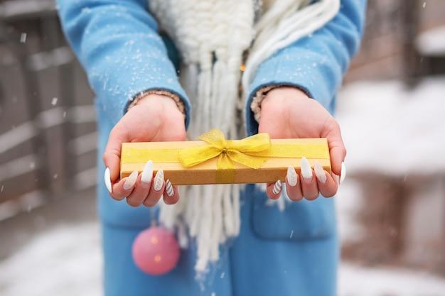 Vrouw gekleed in een warme blauwe jas met een kleine geschenkdoos met een gouden zijden lint op straat met een sneeuwval