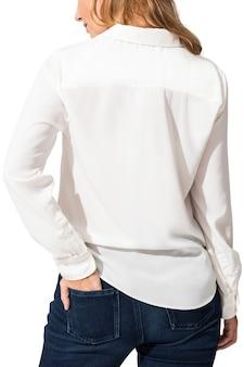 Vrouw, gekleed in een wit shirt met lange mouwen en jeans achteraanzicht