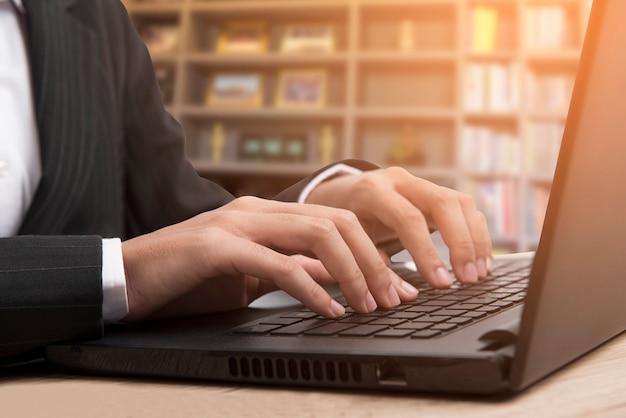 Vrouw, gekleed in een zwart pak, werk toetsen op de laptop.
