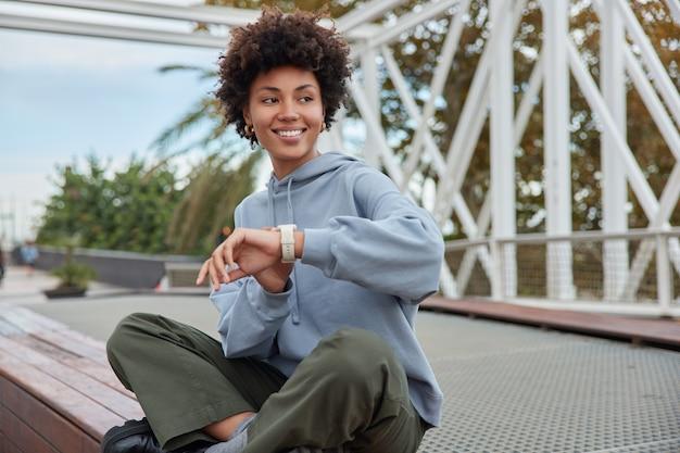 Vrouw gekleed in hoodie en broek zit gekruiste benen buiten controleert de tijd op wacht wacht op vriend heeft een goed humeur tijdens zonnige dag