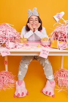Vrouw gekleed in huishoudelijke kleding voelt zich tevreden nadat ze haar taak heeft voltooid, zit op het bureaublad met verschillende stickers en stapels gesneden papier op geel