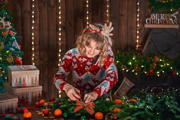 Vrouw gekleed in kerst design trui handgemaakte kerstkrans maken op tafel voor vakantie en nieuwe bestellingen telefonisch accepteert.