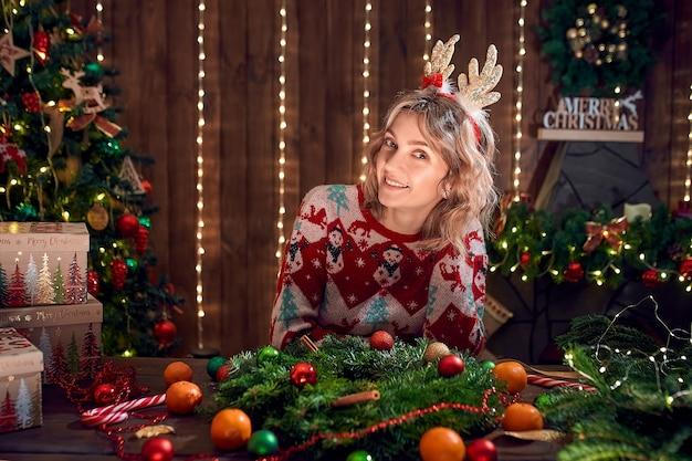 Vrouw gekleed in kerst design trui handgemaakte krans maken