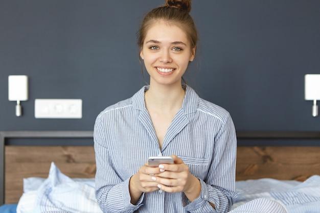 Vrouw gekleed in pyjama zittend in bed