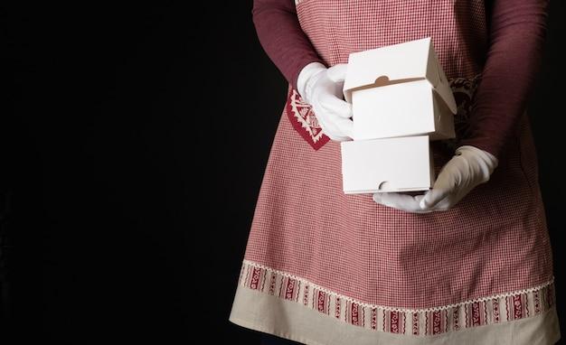 Vrouw gekleed in rode feestelijke schort met geschenkdozen aan de vooravond van nieuwjaar.