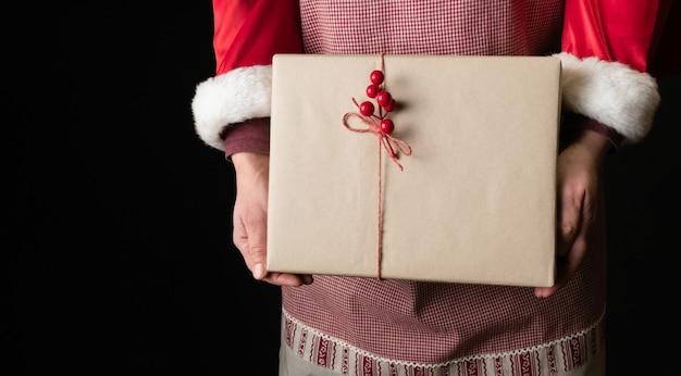 Vrouw gekleed in rode feestelijke schort met gift's box aan de vooravond van nieuwjaar.