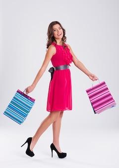Vrouw, gekleed in roze jurk met boodschappentassen