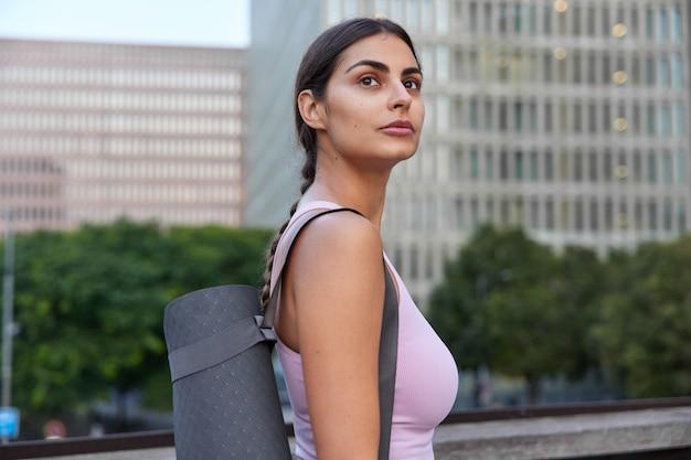 Vrouw gekleed in sportkleding draagt opgerolde yoga pilates rubberen mat loopt buiten poses op gebouw