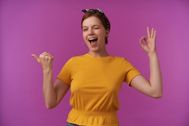 Vrouw, gekleed in stijlvolle zomerkleding en bandana met armen gebaart grote vinger naar links en oke vingers emotie knipoog en lachend naar je blij gezicht op paarse muur