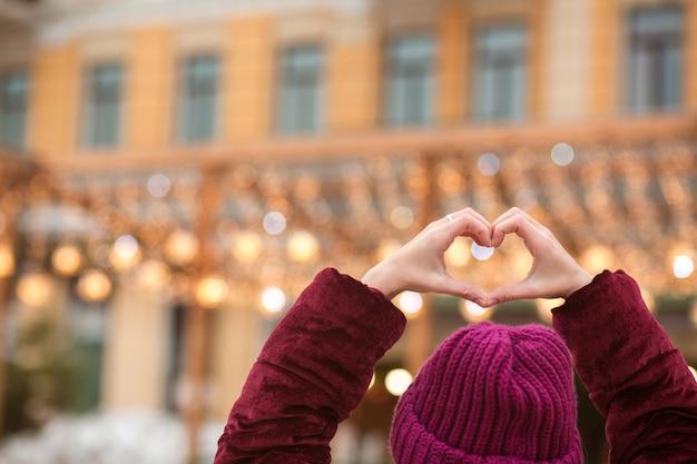 Vrouw gekleed in warme kleding die hartvorm maakt uit haar handen op een achtergrond van stadslichten. ruimte voor tekst