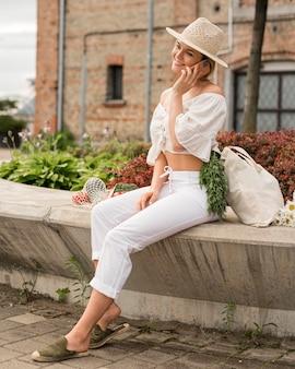 Vrouw, gekleed in wit praten aan de telefoon en zitten