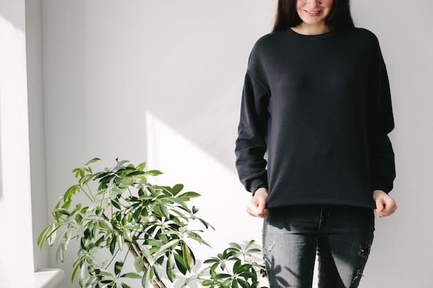 Vrouw, gekleed in zwart sweatshirt dat zich over witte muur bevindt.