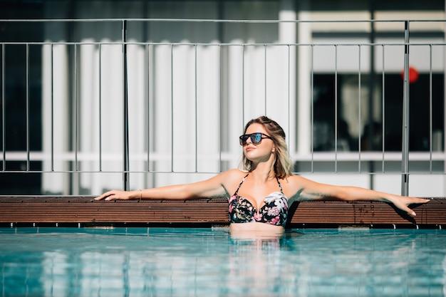 Vrouw, gekleed in zwarte bikini bij het zwembad in de zomer landschap