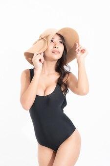 Vrouw, gekleed in zwarte zwemkleding, gekleed in een zonnehoed in de zomer op wit wordt geïsoleerd