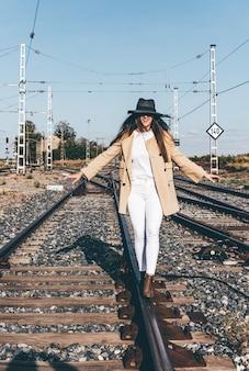 Vrouw gekleed met een beige hoed en jas die langs spoorrails loopt