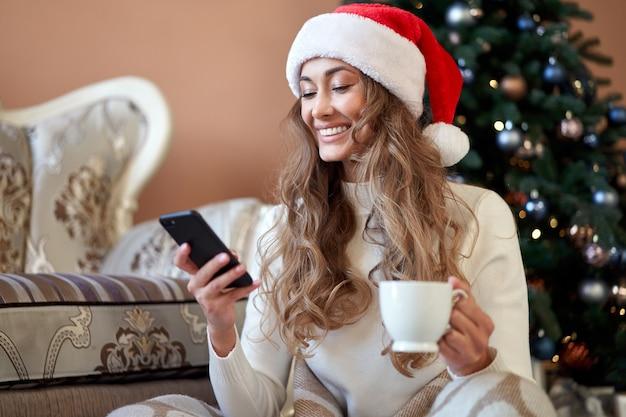 Vrouw gekleed witte trui kerstmuts op de vloer in de buurt van kerstboom met smartpone en kopje koffie