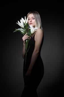 Vrouw gekleurde haarkleur van een blonde met leliebloem op zwarte achtergrond.