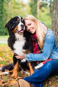Vrouw geknuffel met hond buiten in park