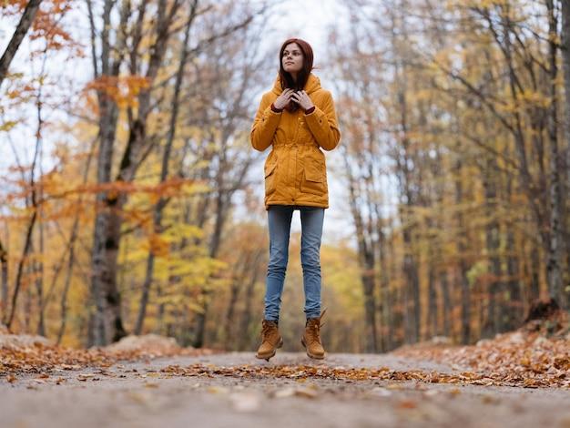 Vrouw gele bladeren herfst bos natuur frisse lucht hoge bomen