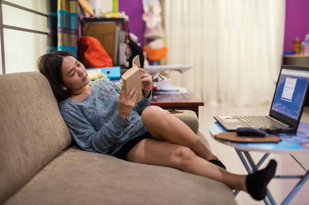 Vrouw gelezen boek op bank van woonkamer