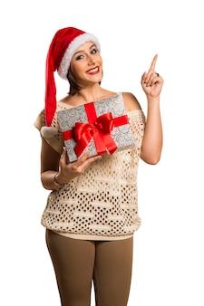 Vrouw gelukkige glimlach wijsvinger met lege kopie ruimte aan de zijkant, jong opgewonden meisje draagt kerstmuts, advertentieproduct geïsoleerd op witte achtergrond
