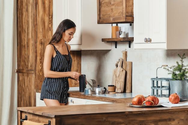 Vrouw gemalen koffie gieten in het koffiezetapparaat