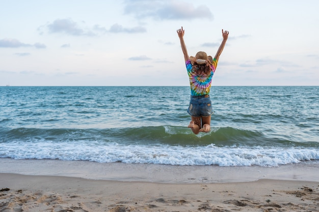 Vrouw geniet en springen op zee strand