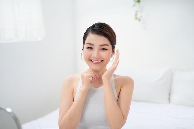 Vrouw geniet met een gezonde stralende huid na dagelijkse schoonheidsroutine en cosmetologiebehandeling.