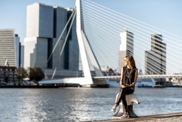 Vrouw geniet 's ochtends van een prachtig uitzicht op de stad op de moderne rivier in de stad rotterdam