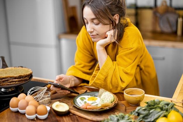 Vrouw geniet 's ochtends van ontbijt in de keuken