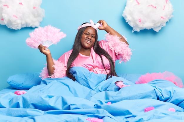Vrouw geniet thuis van een goede dag heeft donker lang haar heft armen op hods fan poseert in comfortabel bed onder blauwe deken heeft een blije uitdrukking